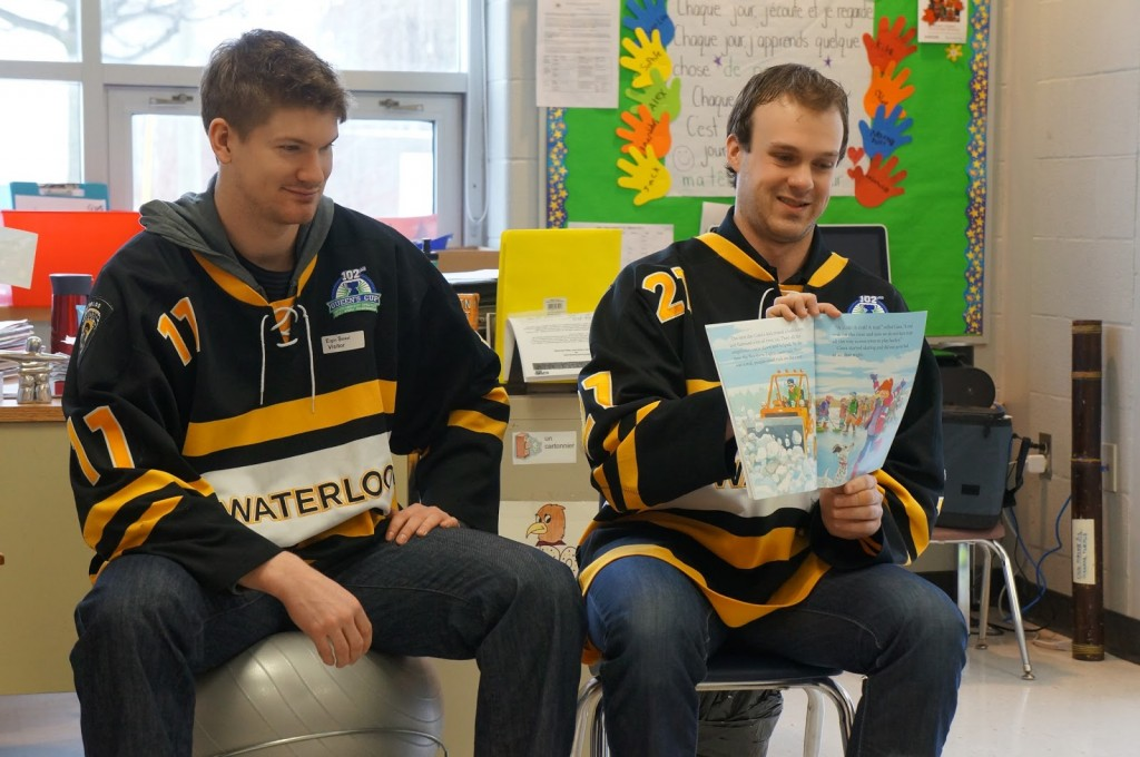 Varsity hockey players reading to elementary school students