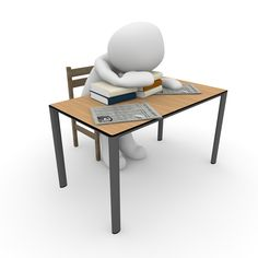 A stressed out figure with head on desk surrounded by books