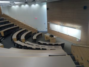 Photo taken at the back of a 200-seat lecture hall looking toward the front white board.