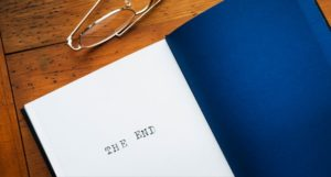 a pair of glasses and a book with a dark blue back cover and the last page showing the words The End sit atop a brown wood desk.